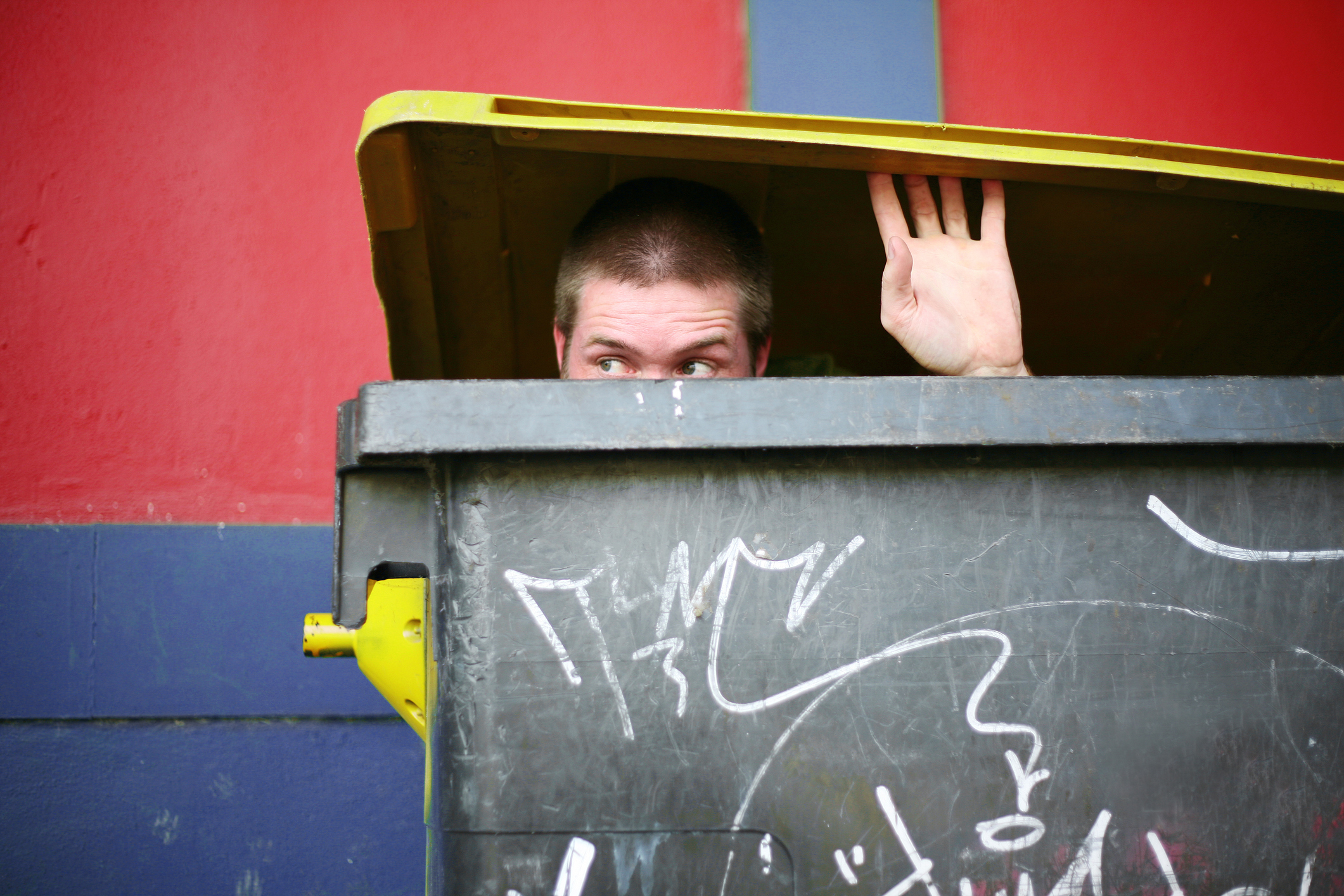 person peeking out of garbage can