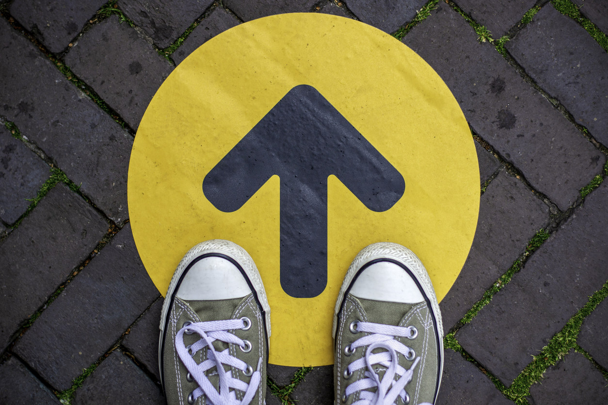 a pair of shoes on to of an arrow pointing forward
