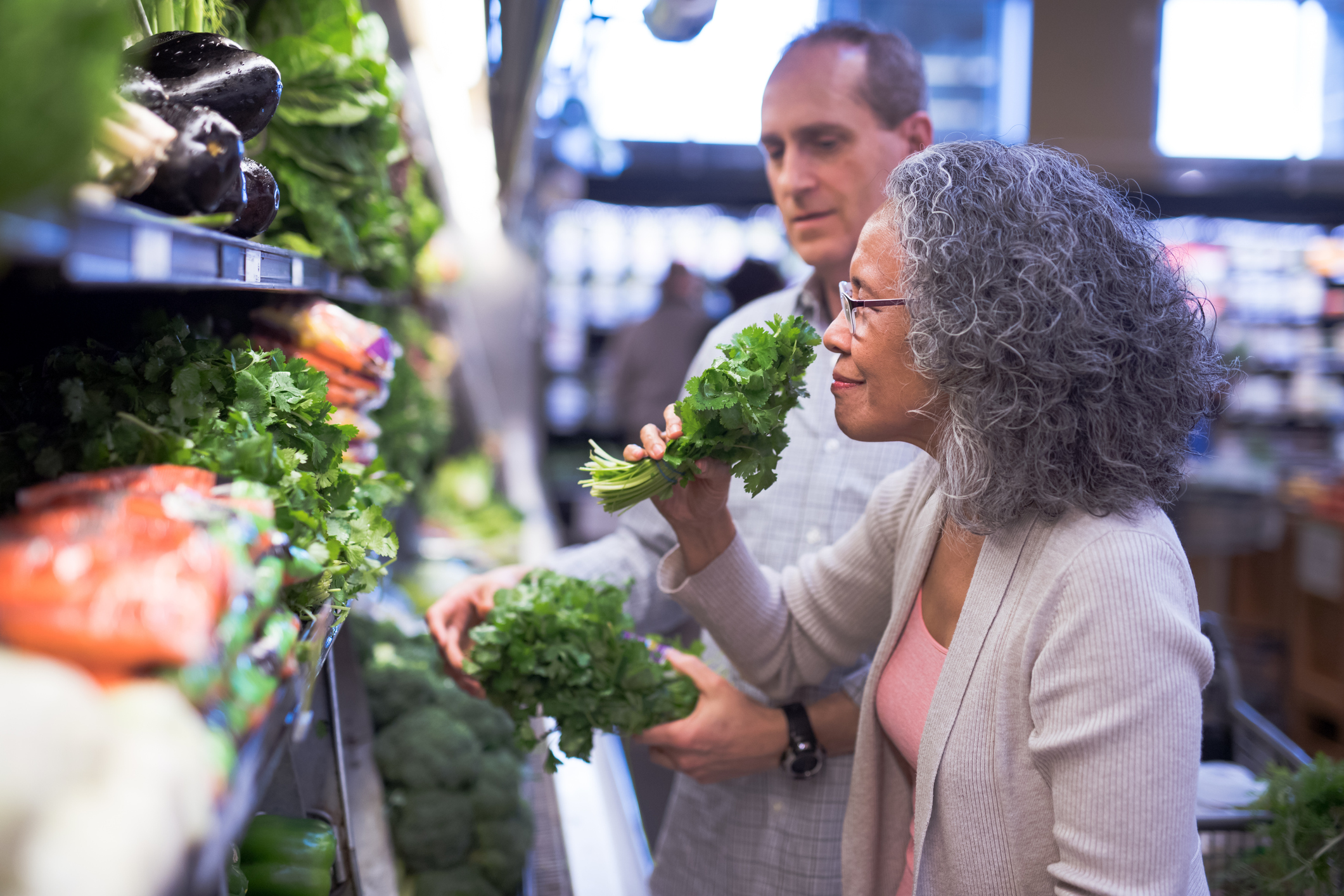 woman smelling kale at a supermarket
