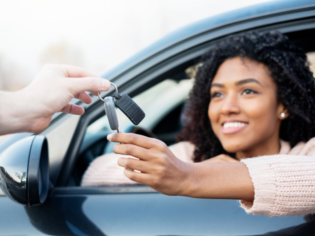 new car buyer taking keys to car
